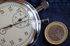Euro muntstuk met een benaming van euro 1 en chronometer op verouderde blauwe denimachtergrond - bedrijfsachtergrond Stock Foto's