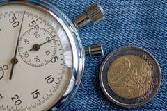 Euro muntstuk met een benaming van euro 2 en chronometer op versleten blauwe denimachtergrond - bedrijfsachtergrond Royalty-vrije Stock Afbeeldingen