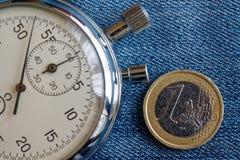 Euro muntstuk met een benaming van euro 1 en chronometer op versleten blauwe denimachtergrond - bedrijfsachtergrond Royalty-vrije Stock Afbeeldingen