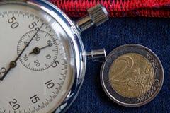 Euro muntstuk met een benaming van euro 2 en chronometer op versleten jeans met rode streepachtergrond - bedrijfsachtergrond Stock Afbeeldingen