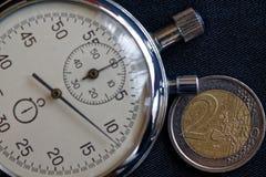 Euro muntstuk met een benaming van euro 2 en chronometer op zwarte denimachtergrond - bedrijfsachtergrond Royalty-vrije Stock Fotografie