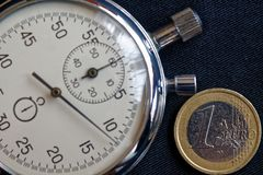 Euro muntstuk met een benaming van euro 1 en chronometer op zwarte denimachtergrond - bedrijfsachtergrond Royalty-vrije Stock Foto's