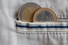 Euro muntstuk met een benaming van 1 en 2 euro in de zak van beige denimjeans met blauwe streep Royalty-vrije Stock Foto