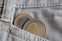 Euro muntstuk met een benaming van 1 en 2 euro in de zak van witte denimjeans Stock Afbeelding