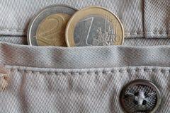 Euro muntstuk met een benaming van 1 en 2 euro in de zak van witte denimjeans met knoop Royalty-vrije Stock Foto's