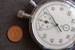 Euro muntstuk met een benaming van 1 eurocent en chronometer op bruine denimachtergrond - bedrijfsachtergrond Stock Fotografie
