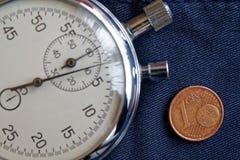 Euro muntstuk met een benaming van 1 eurocent en chronometer op verouderde blauwe denimachtergrond - bedrijfsachtergrond Stock Foto
