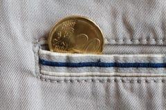 Euro muntstuk met een benaming van 20 eurocenten in de zak van beige denimjeans met blauwe streep Stock Foto's
