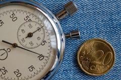Euro muntstuk met een benaming van 20 eurocenten en chronometer op blauwe denimachtergrond - bedrijfsachtergrond Stock Foto's