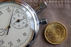 Euro muntstuk met een benaming van 20 eurocenten en chronometer op oude beige jeansachtergrond - bedrijfsachtergrond Royalty-vrije Stock Fotografie