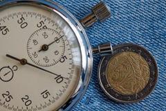 Euro muntstuk met een benaming van euro twee (achterkant) en chronometer op blauwe denimachtergrond - bedrijfsachtergrond Stock Afbeeldingen