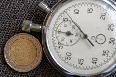 Euro muntstuk met een benaming van euro twee (achterkant) en chronometer op bruine denimachtergrond - bedrijfsachtergrond Royalty-vrije Stock Fotografie