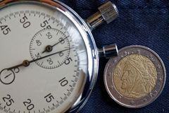 Euro muntstuk met een benaming van euro twee (achterkant) en chronometer op versleten jeansachtergrond - bedrijfsachtergrond Royalty-vrije Stock Foto
