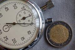 Euro muntstuk met een benaming van euro twee en chronometer op grijze denimachtergrond - bedrijfsachtergrond Royalty-vrije Stock Afbeelding