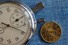 Euro muntstuk met een benaming van twintig eurocenten (achterkant) en chronometer op blauwe denimachtergrond - bedrijfsachtergron Royalty-vrije Stock Foto's