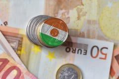 Euro muntstuk met nationale vlag van Niger op de euro achtergrond van geldbankbiljetten Stock Afbeeldingen