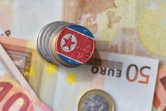 Euro muntstuk met nationale vlag van Noord-Korea op de euro achtergrond van geldbankbiljetten Royalty-vrije Stock Afbeeldingen