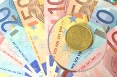 Euro muntstuk onder vergrootglas Stock Afbeeldingen