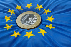 Euro muntstuk op Europese vlag Stock Afbeeldingen