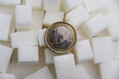Euro muntstuk tussen de close-up van suikerkubussen stock fotografie