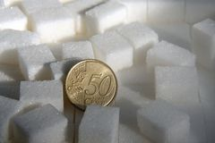Euro muntstuk tussen de close-up van suikerkubussen stock afbeeldingen