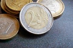 Euro muntstuk twee voor verschillend andere euro muntstukken Stock Foto's