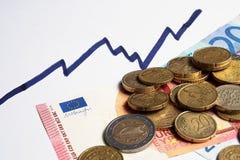 Euro muntstukken en bankbiljetten en toenemende grafieklijn Stock Foto's
