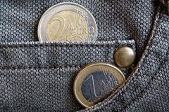 Euro muntstukken met een benaming van één en twee euro in de zak van versleten bruine denimjeans Stock Afbeeldingen