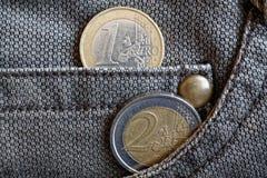 Euro muntstukken met een benaming van 1 en 2 euro in de zak van versleten bruine denimjeans Stock Fotografie