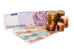 Euro muntstukken op Euro bankbiljetten Stock Foto's