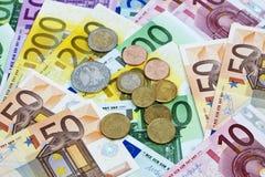 Euro muntstukken op hoop van euro nota's Stock Foto