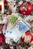 Euro- notas ventiladas perto acima da árvore de Natal no fundo Fotografia de Stock Royalty Free
