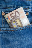 Euro note in a blue jeans pocket. 50 euro note in a blue jeans pocket Royalty Free Stock Photo
