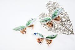 Euro note sotto forma di farfalle sulla foglia brillante decorativa Immagine Stock