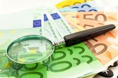 Euro notes avec la calculatrice et la loupe Images stock