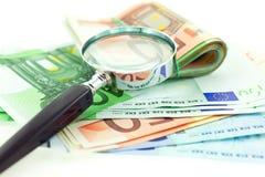 Euro notes avec la loupe sur le fond blanc Photographie stock libre de droits