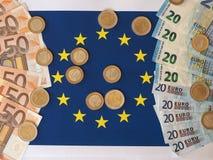 Euro notes and coins, European Union, over flag Royalty Free Stock Photos