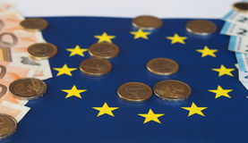 Euro notes and coins, European Union, over flag Royalty Free Stock Photography