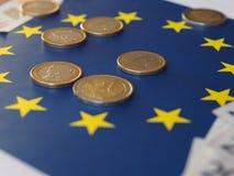 Euro notes and coins, European Union, over flag Stock Photos
