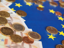 Euro notes and coins, European Union, over flag Stock Image