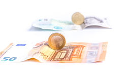 Euro notes and coins in front of British Pound notes and coins Royalty Free Stock Images