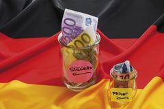 Euro notes dans le récipient sur le drapeau allemand Photographie stock libre de droits