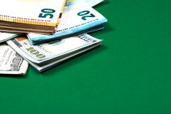 Euro notes and dollar bills on green background royalty free stock images