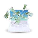 Euro notes flying around the laptop Stock Photos