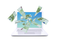 Euro notes flying around the laptop royalty free stock photography
