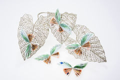 Euro notes in the form of butterflies on decorative glittering leaf. On white background Royalty Free Stock Photography