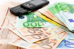 Euro notes and mobile phone on newspaper Royalty Free Stock Photo
