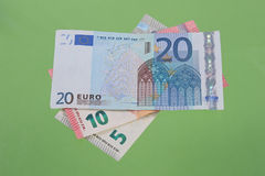 Euro notes on a plain green background. Stock Photos