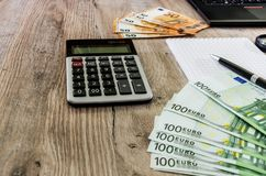 Euro, Notizbuch, Taschenrechner und Teil des Laptops auf einem hölzernen Hintergrund stockfotografie
