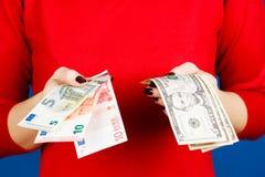 Euro och dolar i händerna av en flicka Arkivfoton